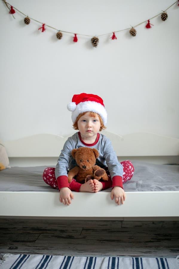 Λυπημένο αγόρι στις πυτζάμες που κάθεται στο κρεβάτι στοκ φωτογραφίες