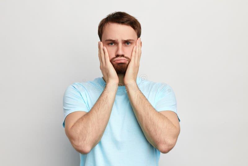 Λυπημένο δυστυχισμένο άτομο με τα χέρια στα μάγουλα που εξετάζει τη κάμερα στοκ εικόνες
