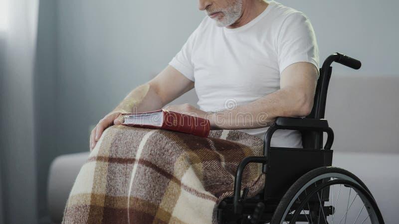 Λυπημένο ενήλικο λεύκωμα αναθεώρησης ατόμων ανάπηρο με τις φωτογραφίες, ελλείποντες συγγενείς στοκ φωτογραφία με δικαίωμα ελεύθερης χρήσης