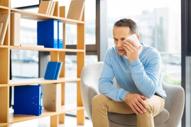 Λυπημένο ευμετάβλητο άτομο που κρατά έναν ιστό εγγράφου στοκ εικόνα