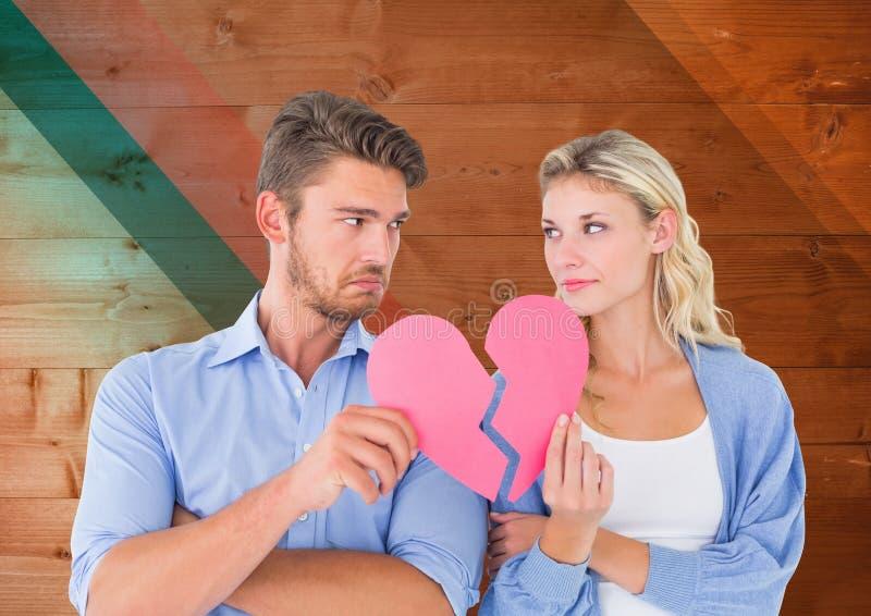 Λυπημένο ζεύγος που φαίνεται μεταξύ τους κρατώντας τις σπασμένες καρδιές στοκ φωτογραφία