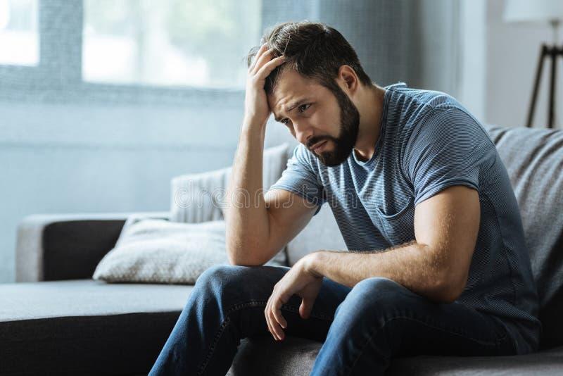 Λυπημένο θλιβερό άτομο που κρατά το μέτωπό του στοκ φωτογραφία με δικαίωμα ελεύθερης χρήσης