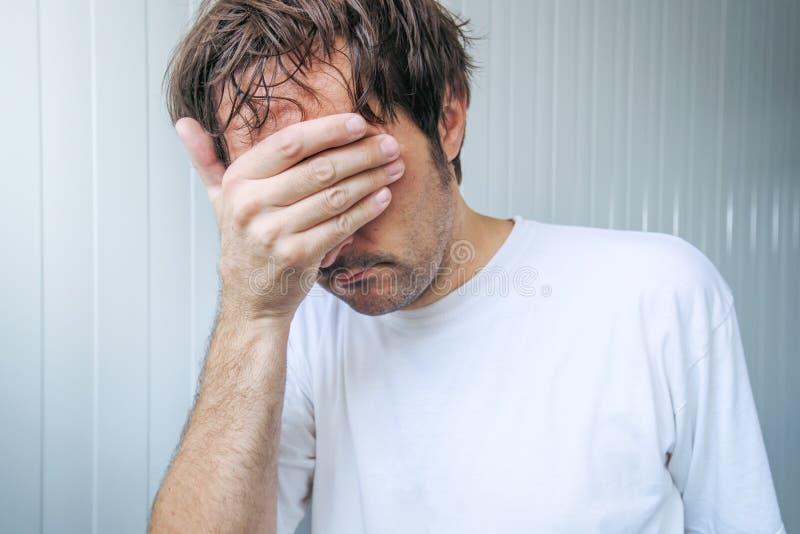 Λυπημένο και μπλε άτομο που καλύπτει το πρόσωπο και να φωνάξει στοκ φωτογραφία με δικαίωμα ελεύθερης χρήσης