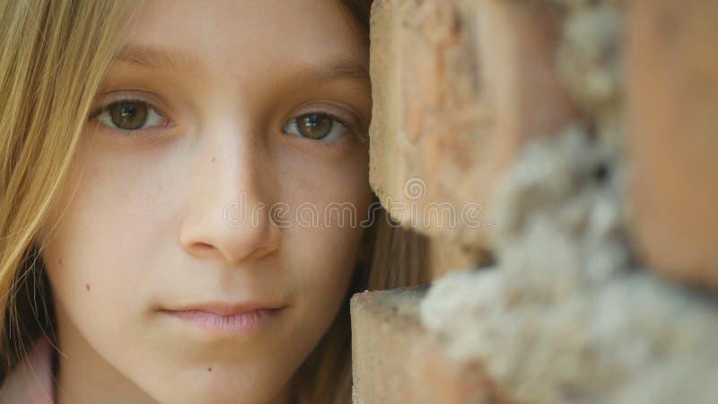 Λυπημένο καταθλιπτικό παιδί που φαίνεται κεκλεισμένων των θυρών, τρυπημένο πορτρέτο κοριτσιών, δυστυχισμένο πρόσωπο παιδιών στοκ φωτογραφία