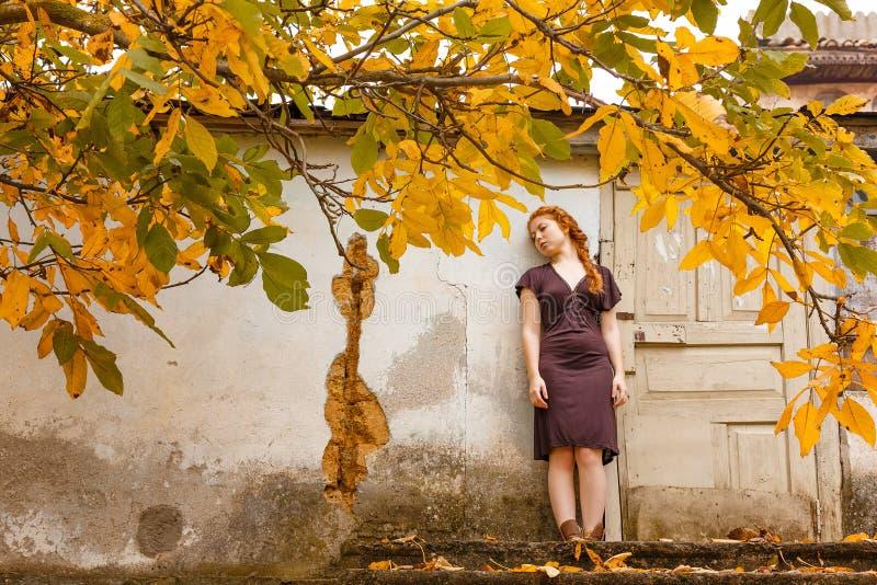 Λυπημένο κοκκινομάλλες κορίτσι που στέκεται κοντά σε ένα σπασμένο παράθυρο, η έννοια της ένδειας και της δυστυχίας στοκ φωτογραφία