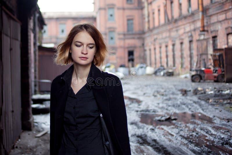Λυπημένο κοκκινομάλλες κορίτσι στο υπόβαθρο του βιομηχανικού τοπίου περπατώντας γυναίκα στοκ εικόνες