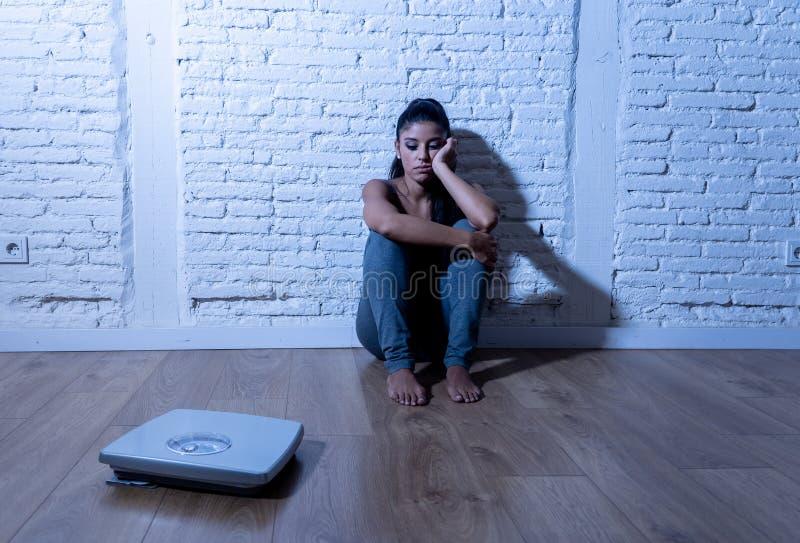 Λυπημένο κορίτσι γυναικών ή εφήβων φοβισμένο του βάρους που εξετάζει την κλίμακα στην αναταραχή διατροφής στοκ φωτογραφία με δικαίωμα ελεύθερης χρήσης