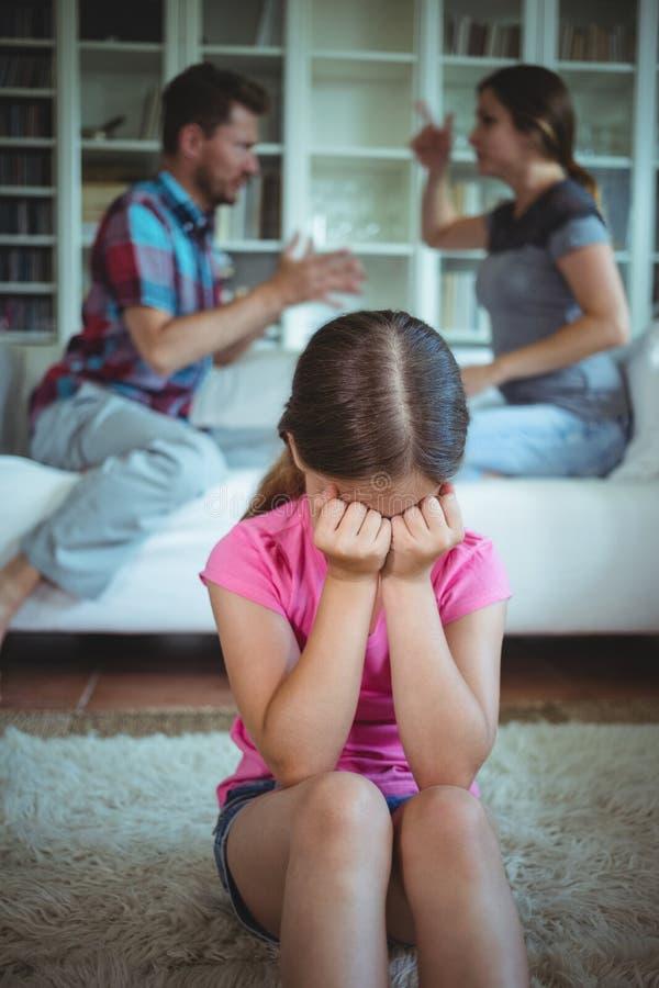 Λυπημένο κορίτσι που φωνάζει ενώ γονείς που υποστηρίζουν στο καθιστικό στοκ εικόνα με δικαίωμα ελεύθερης χρήσης