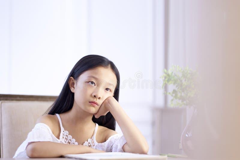 Λυπημένο λίγο ασιατικό κορίτσι κάθεται στη σκέψη γραφείων στοκ φωτογραφία με δικαίωμα ελεύθερης χρήσης