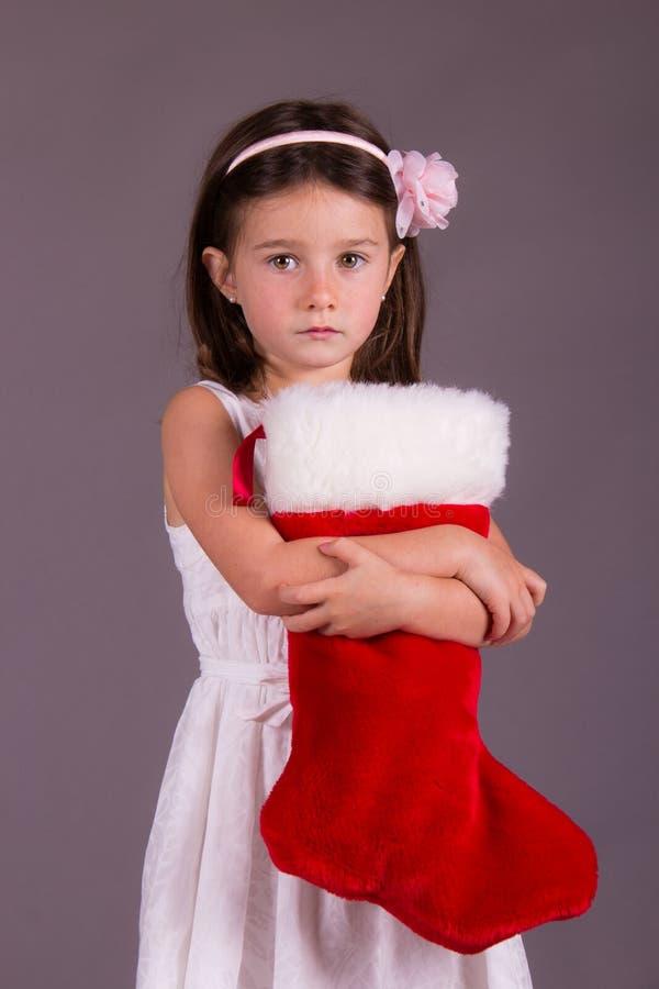 Λυπημένο μικρό κορίτσι με τη γυναικεία κάλτσα Χριστουγέννων στοκ φωτογραφία με δικαίωμα ελεύθερης χρήσης
