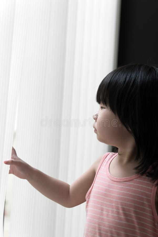 Λυπημένο μικρό κορίτσι που εξετάζει το παράθυρο στοκ εικόνα