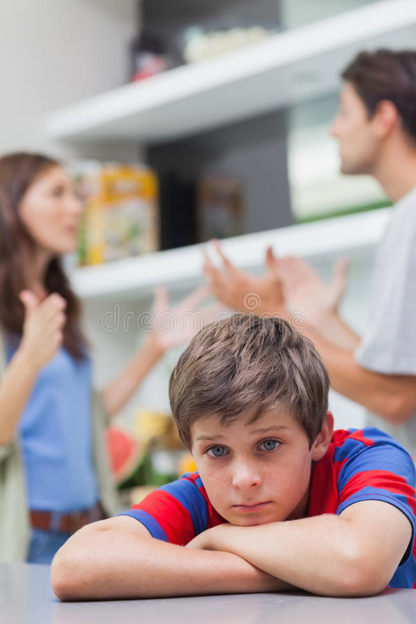 Λυπημένο μικρό παιδί που ακούει να υποστηρίξει γονέων του στοκ φωτογραφία