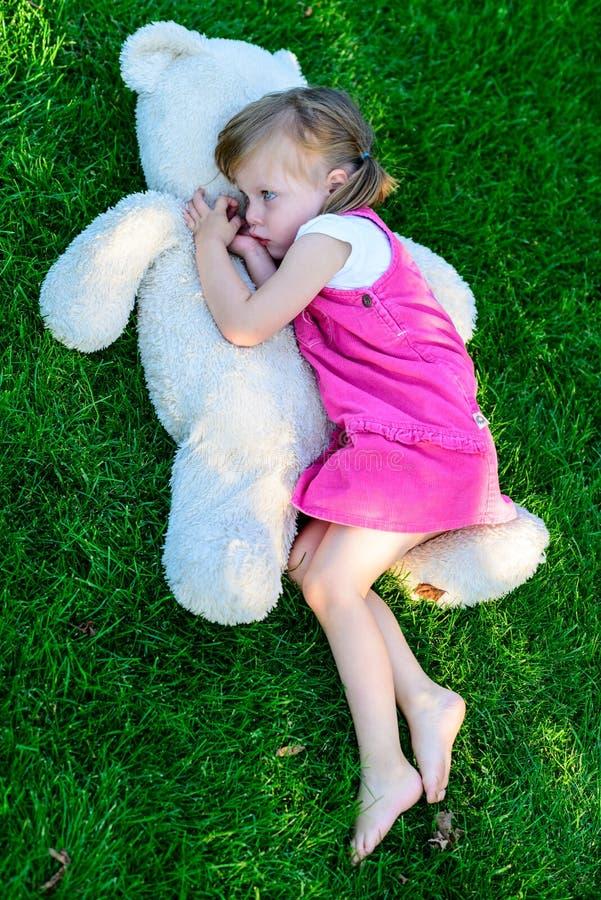 Λυπημένο να βρεθεί μικρών κοριτσιών στη χλόη με μεγάλο teddy αντέχει στοκ εικόνες