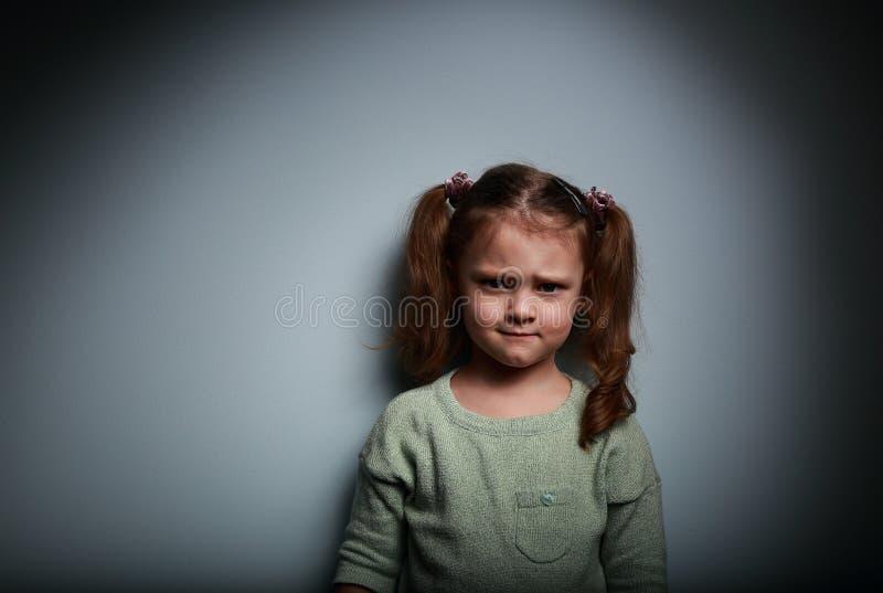 Λυπημένο παιδί θυμού που κοιτάζει στο σκοτεινό υπόβαθρο στοκ φωτογραφίες
