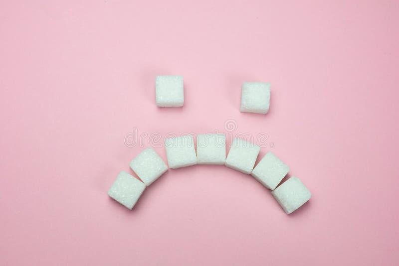 Λυπημένο πρόσωπο της άσπρης ζάχαρης σε ένα ρόδινο υπόβαθρο στοκ εικόνα