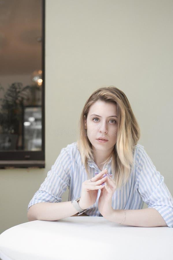 Λυπημένο σκεπτικό κορίτσι σε έναν πίνακα σε έναν καφέ στοκ φωτογραφία με δικαίωμα ελεύθερης χρήσης