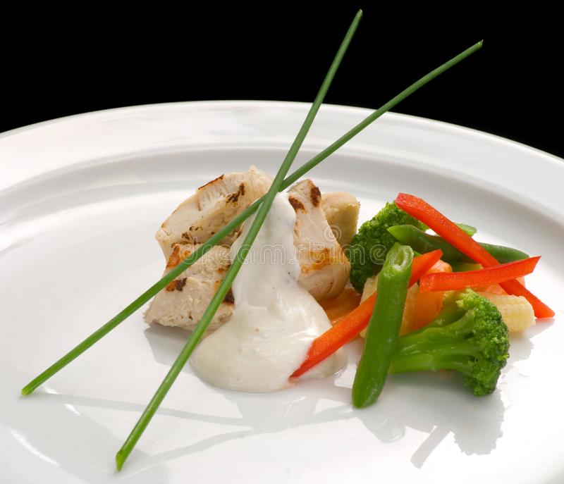 λωρίδα κοτόπουλου, βρασμένες στον ατμό λαχανικά και σάλτσα γιαουρτιού σε ένα πιάτο, κινηματογράφηση σε πρώτο πλάνο στοκ φωτογραφίες