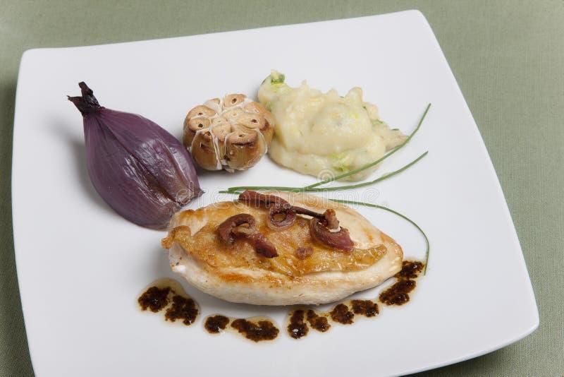 Λωρίδα κοτόπουλου, τηγανισμένα κρεμμύδια και σκόρδο στοκ φωτογραφίες