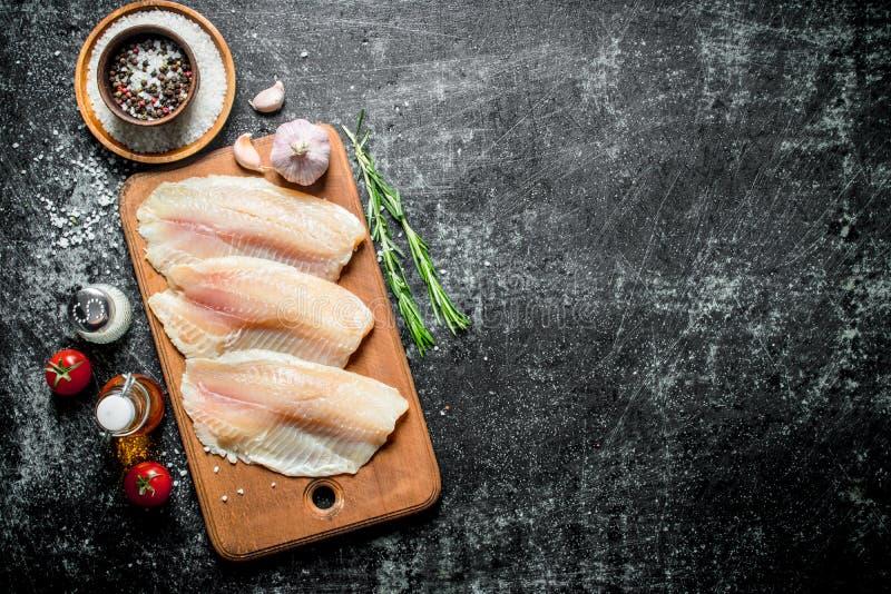 Λωρίδα ψαριών με τα καρυκεύματα, το δεντρολίβανο, το σκόρδο και το έλαιο στο μπουκάλι στοκ εικόνα με δικαίωμα ελεύθερης χρήσης