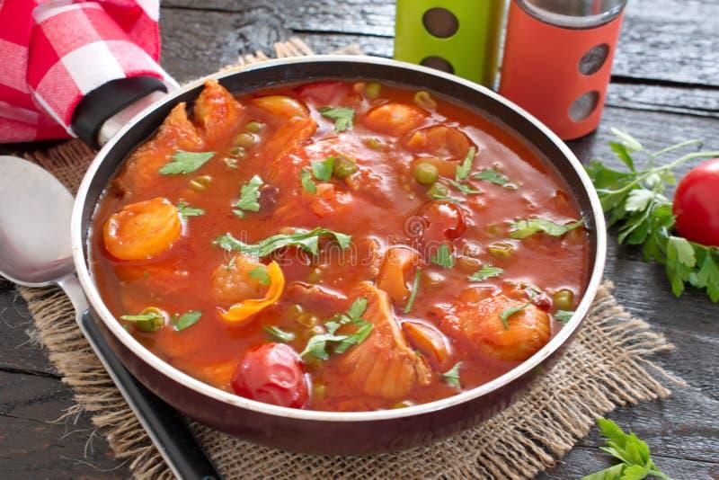 Λωρίδα ψαριών που μαγειρεύεται στη σάλτσα ντοματών με τα πράσινα μπιζέλια και τις ντομάτες κερασιών σε ένα πιάτο σε ένα ξύλινο υπ στοκ εικόνες
