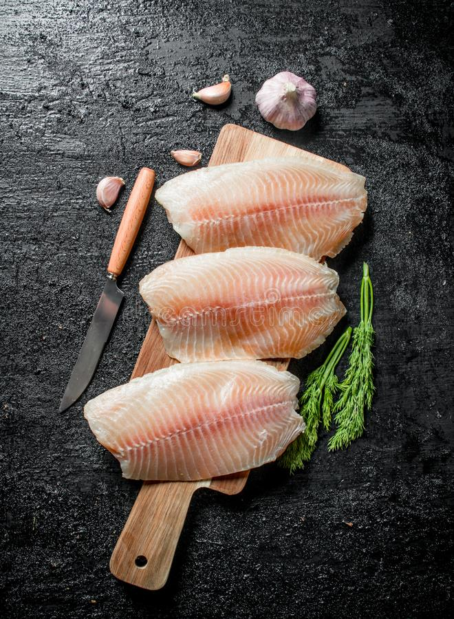 Λωρίδα ψαριών σε έναν πίνακα κοπής με ένα μαχαίρι, έναν άνηθο και ένα σκόρδο στοκ φωτογραφία