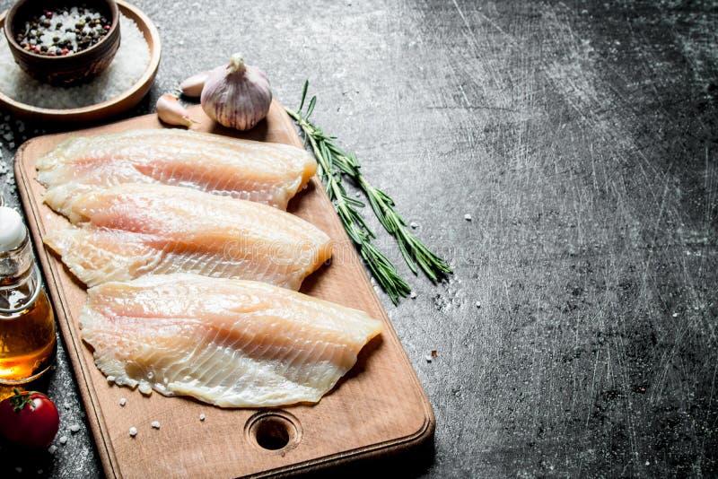 Λωρίδα ψαριών σε έναν πίνακα κοπής με το δεντρολίβανο, το σκόρδο και τα καρυκεύματα σε ένα κύπελλο στοκ εικόνες