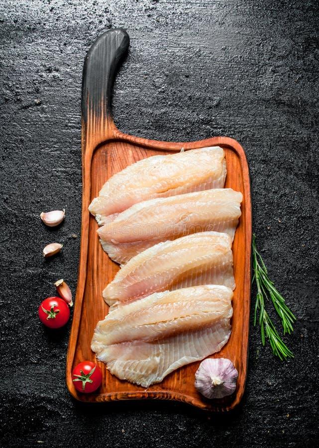 Λωρίδα ψαριών σε έναν πίνακα κοπής με το δεντρολίβανο, το σκόρδο και τις ντομάτες στοκ φωτογραφία με δικαίωμα ελεύθερης χρήσης