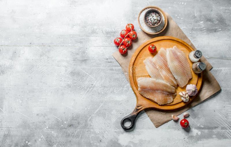 Λωρίδα ψαριών σε έναν στρογγυλό τέμνοντα πίνακα με τα καρυκεύματα, τις ντομάτες και το σκόρδο στοκ φωτογραφία με δικαίωμα ελεύθερης χρήσης