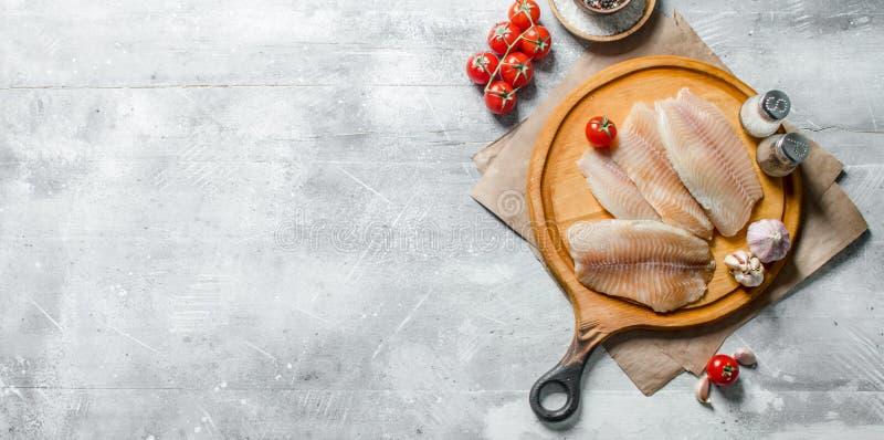 Λωρίδα ψαριών σε έναν στρογγυλό τέμνοντα πίνακα με τα καρυκεύματα, τις ντομάτες και το σκόρδο στοκ φωτογραφίες με δικαίωμα ελεύθερης χρήσης