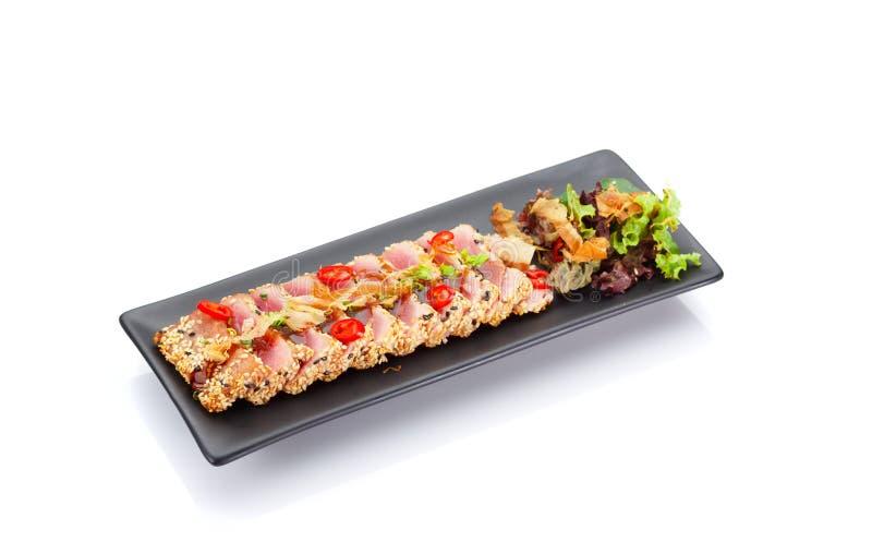 Λωρίδα τόνου φρέσκια που τηγανίζει με το σουσάμι και που εξυπηρετείται σε ένα μαύρο πιάτο στοκ εικόνες