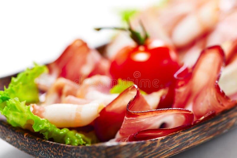 Λωρίδες μπέϊκον που εξυπηρετούνται με τα πράσινα και την ντομάτα. Στο άσπρο υπόβαθρο στοκ εικόνα με δικαίωμα ελεύθερης χρήσης
