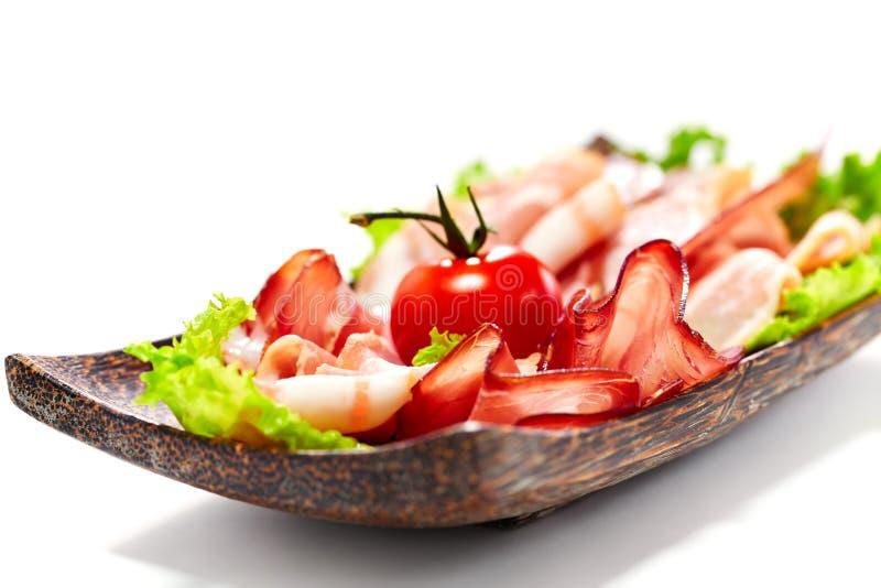 Λωρίδες μπέϊκον που εξυπηρετούνται με τα πράσινα και την ντομάτα. Απομονωμένος στο λευκό. στοκ εικόνες με δικαίωμα ελεύθερης χρήσης