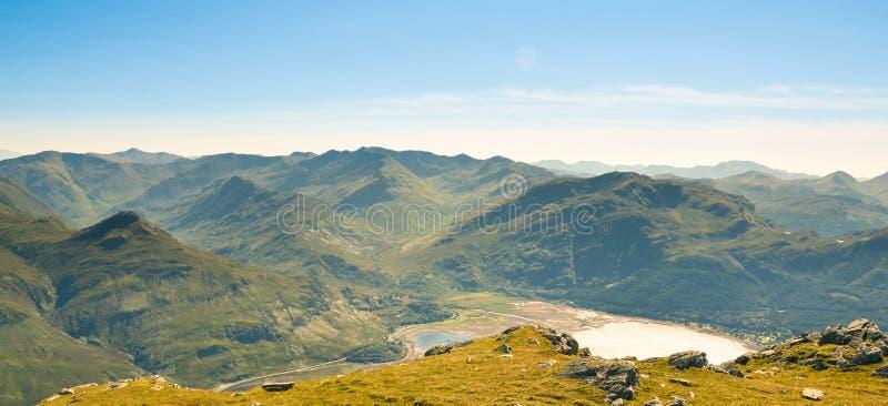 Λόφοι και βουνά κάτω από το όμορφο φως από μέσα από τα σύννεφα και το πράσινο δυτικό Χάιλαντς λόφων στη Σκωτία, που ενώνεται στοκ φωτογραφία
