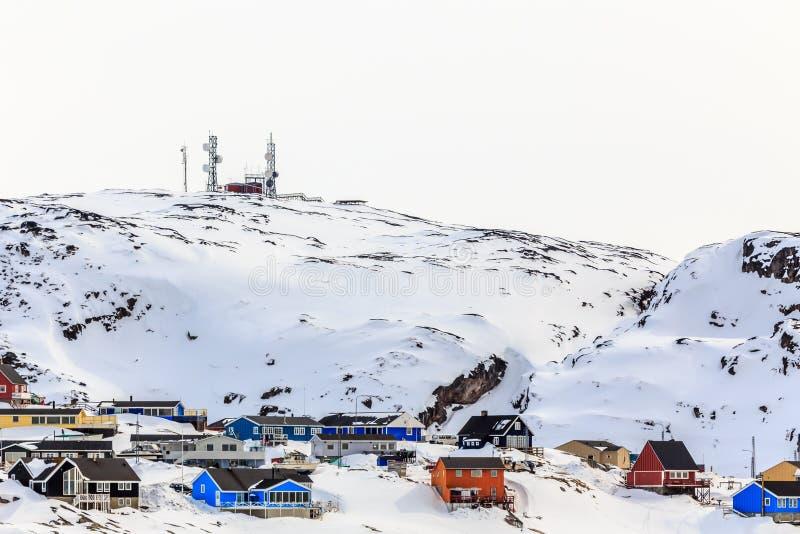 Λόφος χιονιού με τα σπίτια Inuit και τις κεραίες στην κορυφή, Ιλούλισσατ γ στοκ φωτογραφία
