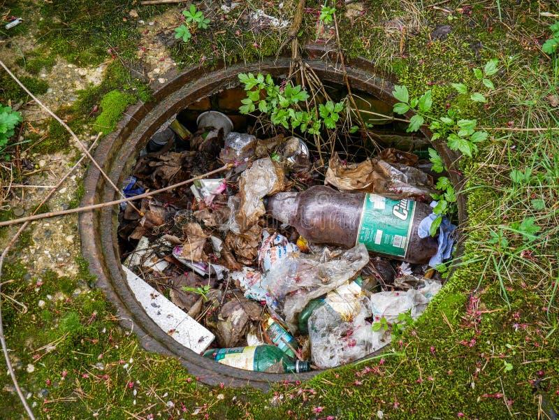 Λύματα χωρίς μια κάλυψη που γεμίζουν με το πλαστικά μπουκάλι μπύρας και τα απορρίμματα στοκ εικόνες με δικαίωμα ελεύθερης χρήσης