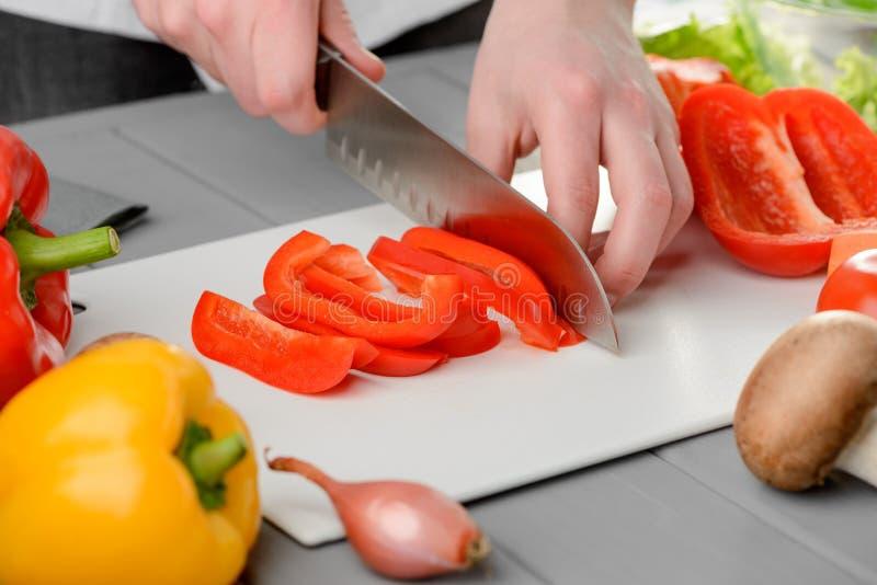 Μάγειρας αρχιμαγείρων που κόβει ένα πιπέρι στοκ εικόνες με δικαίωμα ελεύθερης χρήσης
