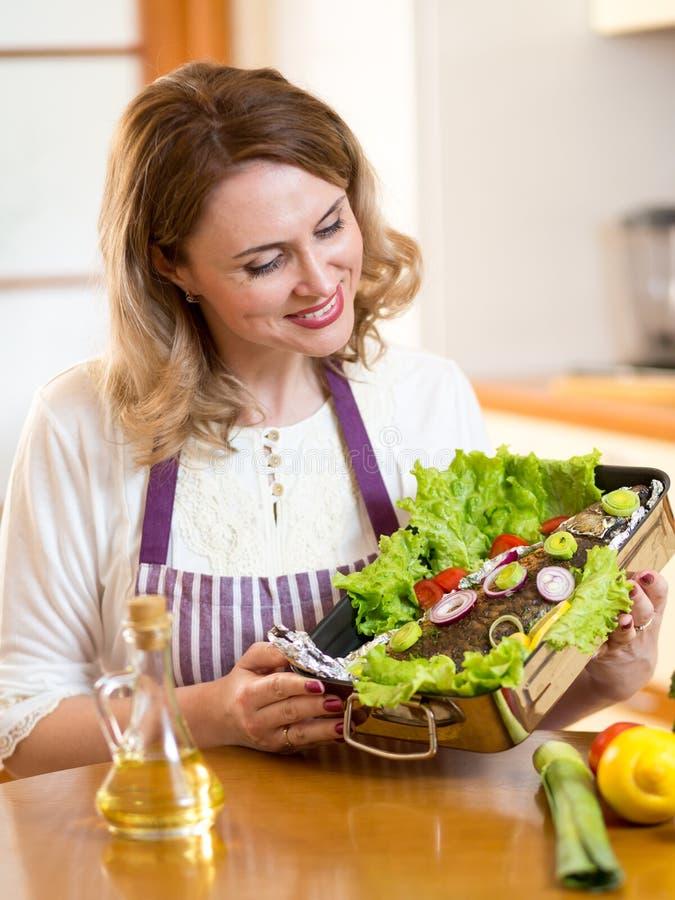 Μάγειρας - μέσης ηλικίας ψάρια σχαρών γυναικών στην κουζίνα στοκ φωτογραφίες