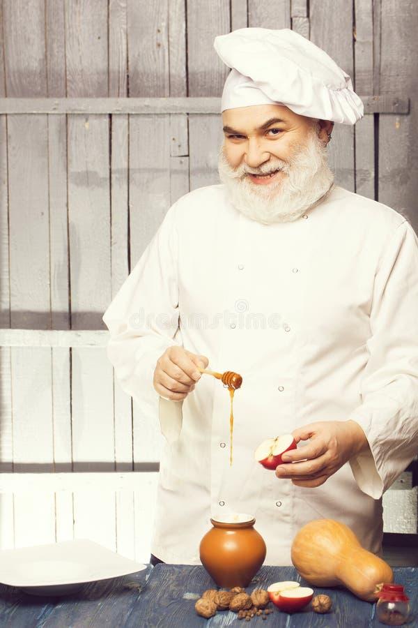 Μάγειρας με το μέλι και τα τρόφιμα στοκ φωτογραφία