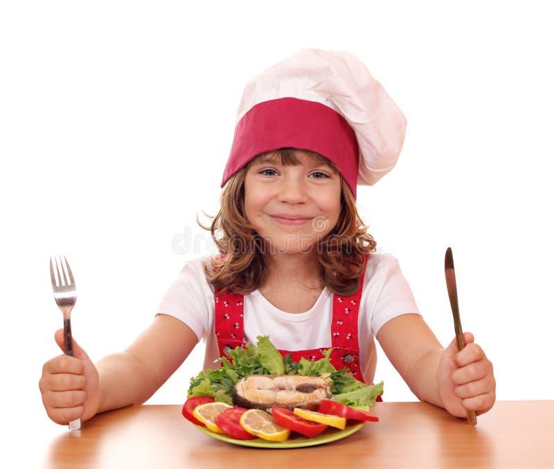 Μάγειρας μικρών κοριτσιών με τα θαλασσινά σολομών στοκ εικόνα με δικαίωμα ελεύθερης χρήσης