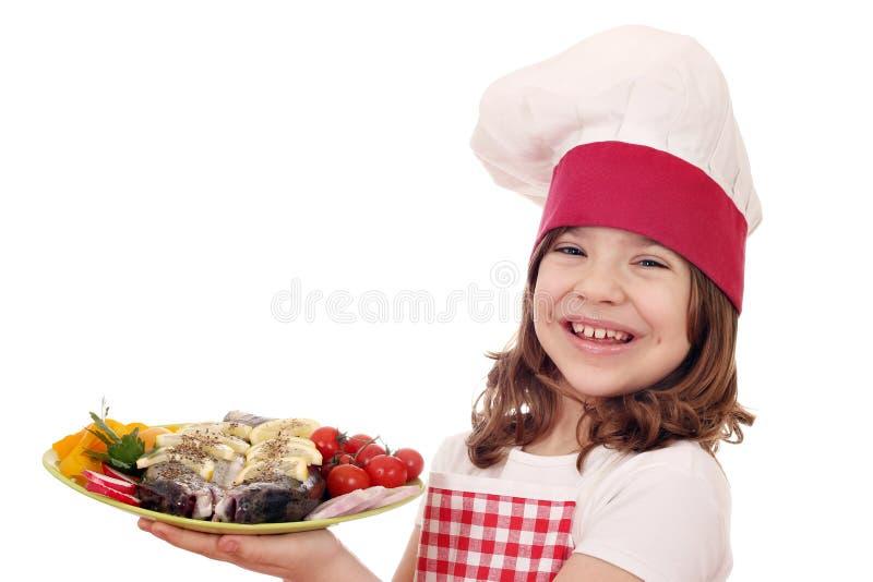 Μάγειρας μικρών κοριτσιών με τα ψάρια πεστροφών και σαλάτα στο πιάτο στοκ φωτογραφία με δικαίωμα ελεύθερης χρήσης