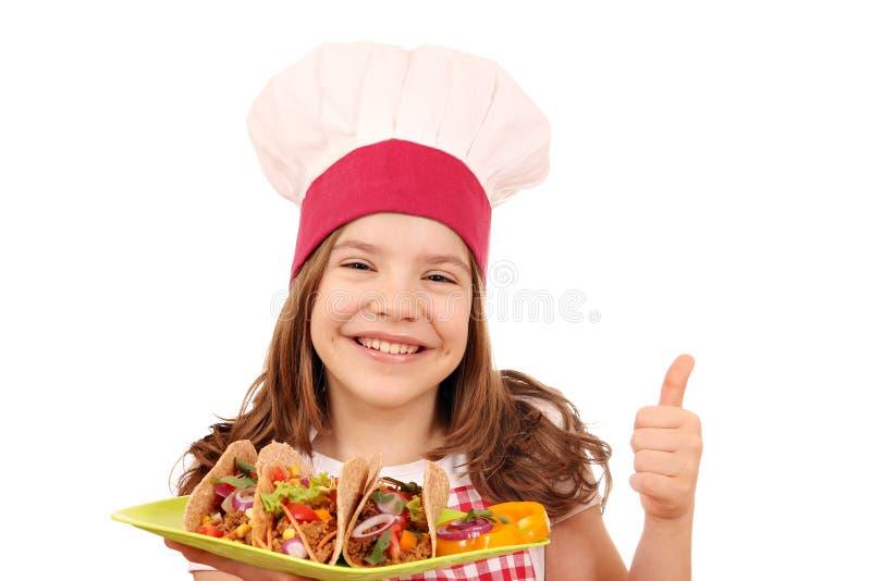 Μάγειρας μικρών κοριτσιών με τα tacos και τον αντίχειρα επάνω στοκ εικόνες με δικαίωμα ελεύθερης χρήσης