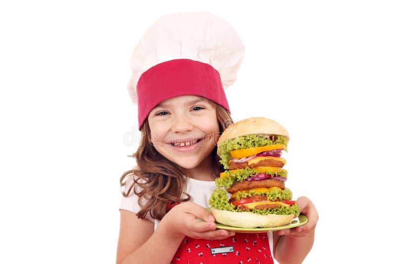 Μάγειρας μικρών κοριτσιών με το μεγάλο χάμπουργκερ στοκ φωτογραφία με δικαίωμα ελεύθερης χρήσης
