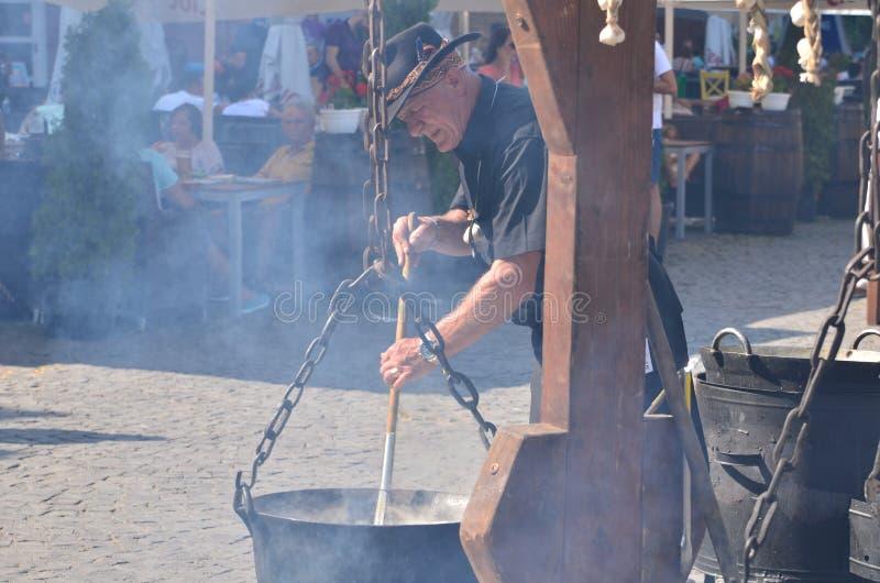 Μάγειρας που προετοιμάζει τα τρόφιμα στην πυρκαγιά υπαίθρια στοκ φωτογραφίες