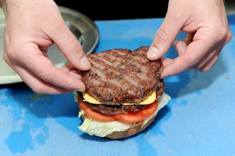 Μάγειρας που προσθέτει burger στα έτοιμα κουλούρια για το χάμπουργκερ Προετοιμασία και κατασκευή του χάμπουργκερ στοκ φωτογραφία με δικαίωμα ελεύθερης χρήσης