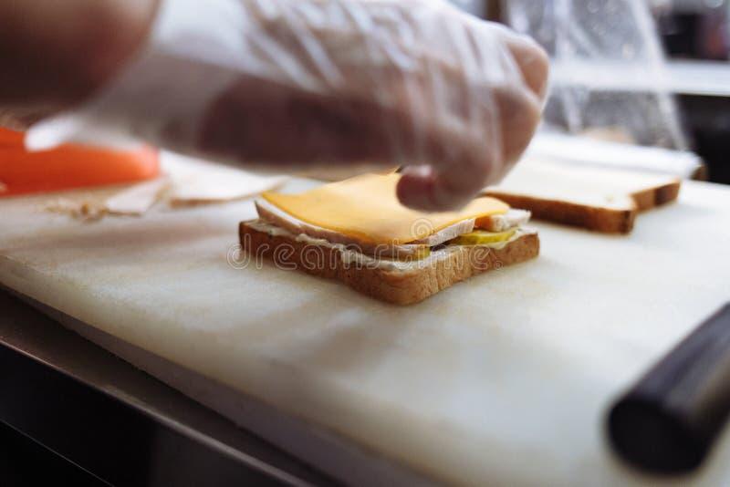 Μάγειρας στα γάντια πολυαιθυλενίου που κατασκευάζει ένα σάντουιτς σε έναν λευκό πίνακα στοκ εικόνες