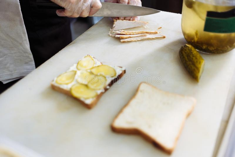 Μάγειρας στα γάντια πολυαιθυλενίου που κατασκευάζει ένα σάντουιτς σε έναν λευκό πίνακα στοκ εικόνα