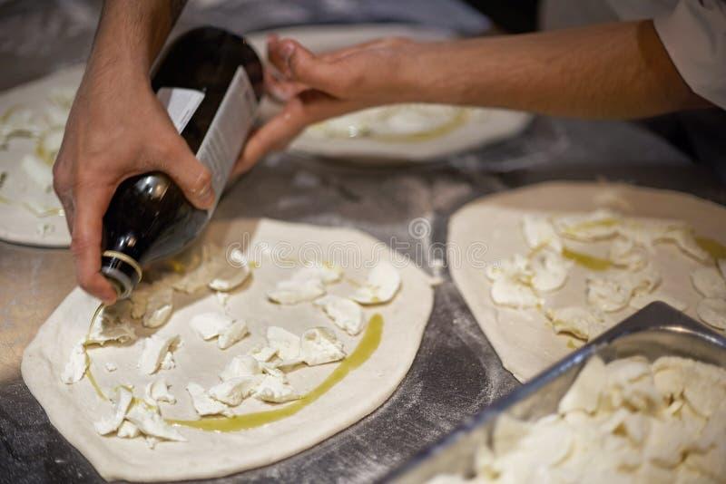 Μάγειρας στην κουζίνα που βάζει τα συστατικά στην πίτσα Έννοια πιτσών Παραγωγή και παράδοση των τροφίμων στοκ φωτογραφίες