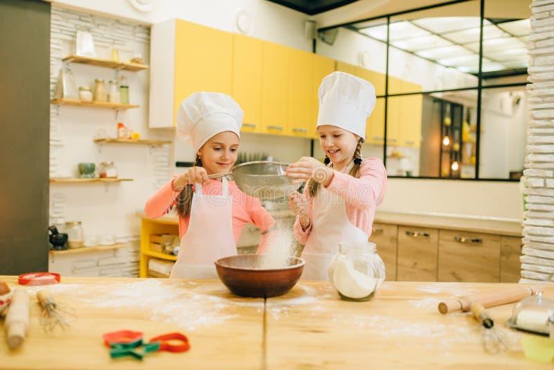 Μάγειρες κοριτσιών, προετοιμασία μπισκότων στην κουζίνα στοκ εικόνες