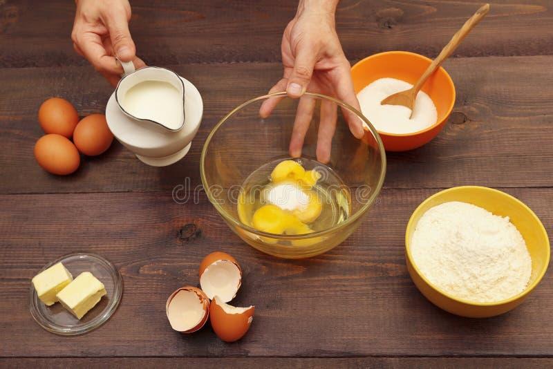 Μάγειρες που χύνουν γάλα σε ένα μπολ για να φτιάξουν ζύμη σε ξύλινο τραπέζι στοκ εικόνες