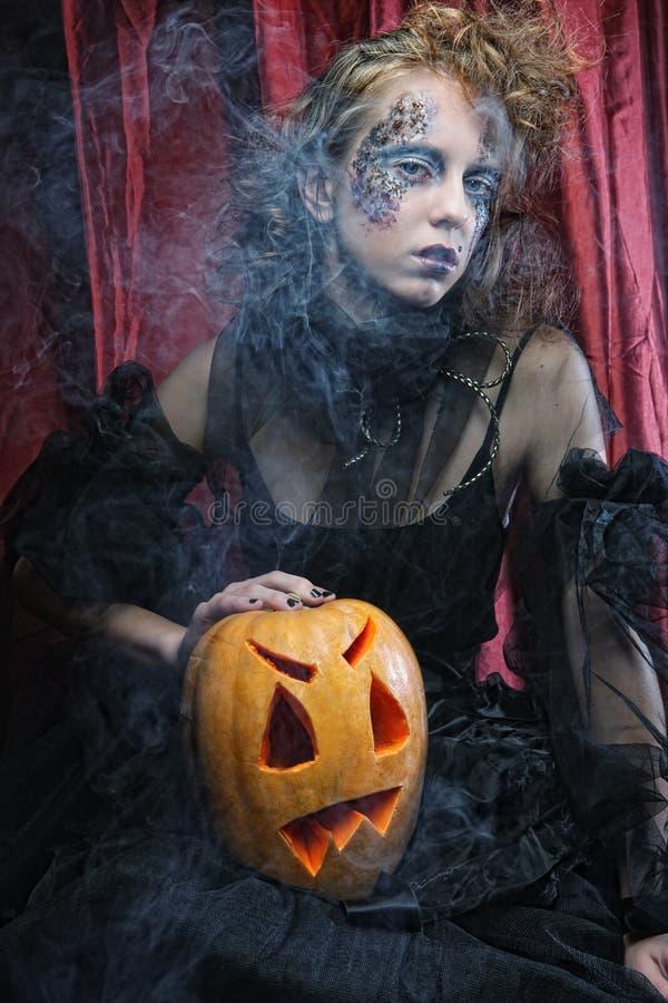 Μάγισσα αποκριών με τη χαρασμένη κολοκύθα πέρα από το κόκκινο υπόβαθρο στοκ εικόνα